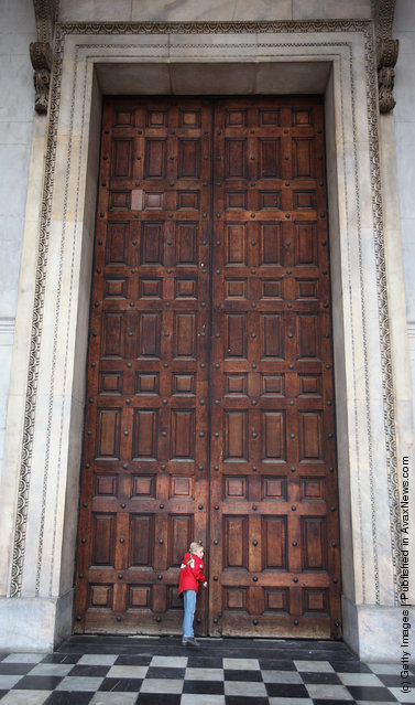 A girl listens at the closed west door of St Paul's Cathedral