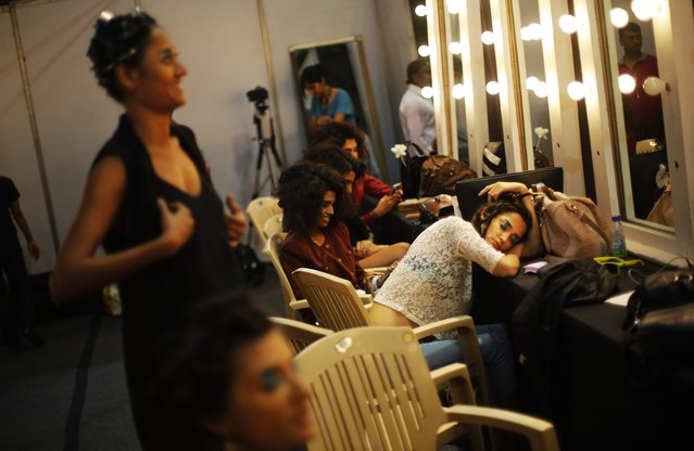Models take break backstage on the final day of the Wills Lifestyle India Fashion Week in New Delhi, India, Sunday, March 30, 2014. (Photo by Altaf Qadri/AP Photo)