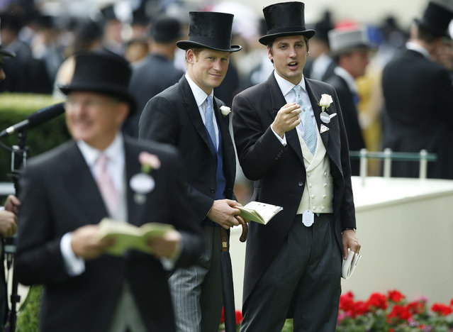 Britain's Prince Harry, center, is accompanied by his friend Jake Warren on the first day of  Royal Ascot horse racing meet at Ascot, England, Tuesday, June 16, 2015. Royal Ascot is the annual five day horse race meeting that Britain's Queen Elizabeth II attends every day of the event. (AP Photo/Alastair Grant)