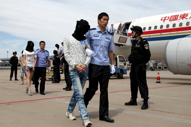 Suspects involved in cross border telecom fraud walk off a plane after being repatriated from overseas, at an airport in Beijing, China, May 24, 2012. (Photo by Reuters/China Daily)