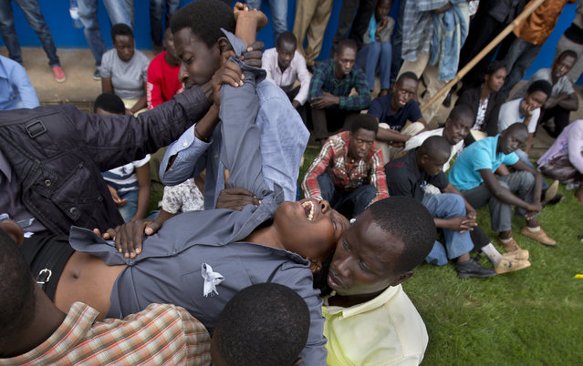 A wailing and distraught Rwandan woman, one of dozens overcome by grief at recalling the horror of the genocide, is carried away to receive help during a public ceremony to mark the 20th anniversary of the Rwandan genocide, at Amahoro stadium in Kigali, Rwanda Monday, April 7, 2014. (Photo by Ben Curtis/AP Photo)