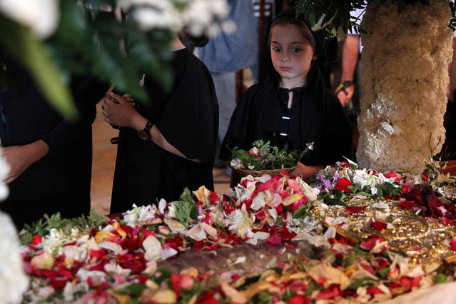 A Greek Cypriot orthodox faithful girl stands next to an Epitaph during a Good Friday mass at a church of Ayios Georgios Exorinos in Famagusta, in the Turkish-administered northern part of Cyprus, April 29, 2016. (Photo by Yiannis Kourtoglou/Reuters)