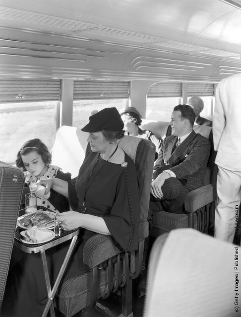Passengers relaxing with a cooked meal on the Illinois Central streamline diesel train 'Green Diamond', circa 1935