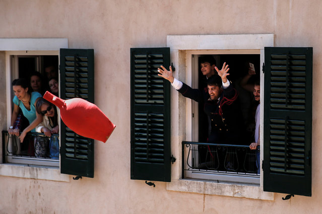"A man throws a clay pot during the Greek Orthodox Easter tradition of ""Botides"" on Holy Saturday marking the so-called ""First Resurrection"", on the island of Corfu, Greece, April 30, 2016. (Photo by Alkis Konstantinidis/Reuters)"