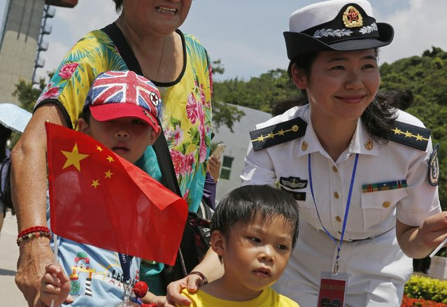 Visitors pose with a Chinese People's Liberation Army (PLA) personnel at the open day of Stonecutter Island Navy Base in Hong Kong to mark the 18th anniversary of the Hong Kong handover to China in Hong Kong, Wednesday, July 1, 2015. (Photo by Kin Cheung/AP Photo)