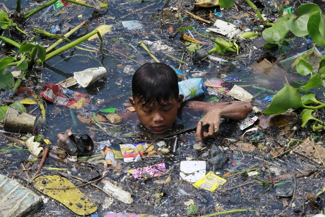 A boy sift through floating garbage as he collect recyclable materials in a polluted river at Navotas city, north of Manila, July 2, 2015. (Photo by Romeo Ranoco/Reuters)