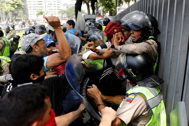 Demonstrators scuffle with security forces during an opposition rally in Caracas, Venezuela on April 4, 2017. (Photo by Carlos Garcia Rawlins/Reuters)