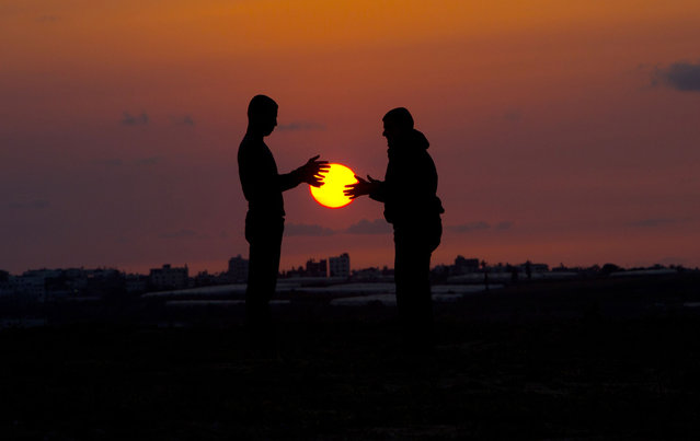 Palestinian youths play as the sun sets in Beit Hanun in the northern Gaza Strip on April 9, 2014. (Photo by Mahmud Hams/AFP Photo)