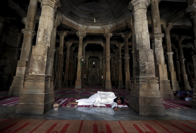 A Muslim man takes a nap after offering prayers inside a mosque during the holy month of Ramadan in Ahmedabad, India, June 30, 2015. (Photo by Amit Dave/Reuters)