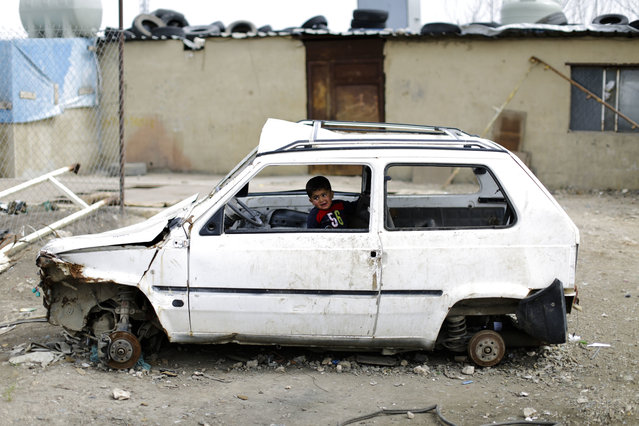A Syrian refugee boy plays inside a ruin car at an informal refugee camp, at Al-Marj town in Bekaa valley, east Lebanon Lebanon, Saturday, April 8, 2017. For the millions of Syrian refugees scattered across camps and illegal settlements across the region, the chemical attack on a town in northern Syria and subsequent U.S. strike was a rare moment when the world briefly turned its attention to Syria, before turning away again. (Photo by Hassan Ammar/AP Photo)