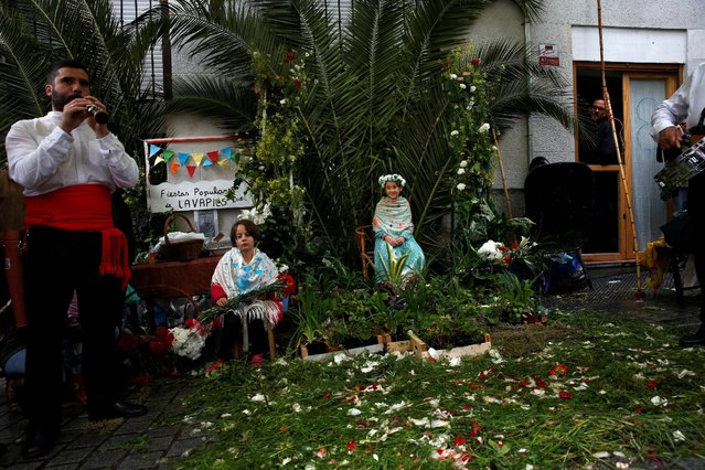 """Maya"" girl Lucinda Usaola, 8, (R), sits with her friend Candela Garcia, 6, at an altar during ""Las Mayas"" festivity in Madrid, Spain, May 8, 2016. (Photo by Susana Vera/Reuters)"