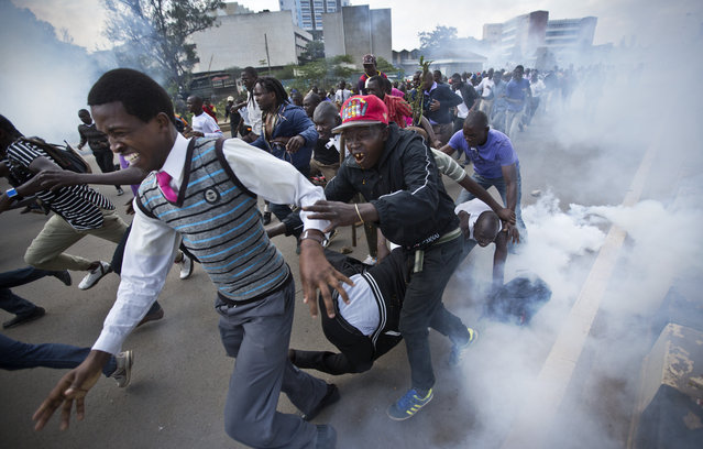 Opposition supporters flee from tear gas grenades fired by riot police, during a protest in downtown Nairobi, Kenya Monday, May 16, 2016. (Photo by Ben Curtis/AP Photo)