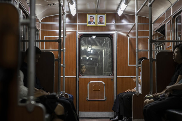 A child looks through a window separating subway train carriages beneath the portraits of late North Korean leaders Kim Il Sung and Kim Jong Il in Pyongyang on June 17, 2019. (Photo by Ed Jones/AFP Photo)