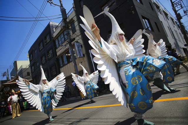 Heron-hooded dancers perform as they parade down the streets toward Asakusa Shrine in the compound of Sensoji Temple in Tokyo at the annual Sanja Festival, on May 16, 2014. (Photo by Eugene Hoshiko/Associated Press)