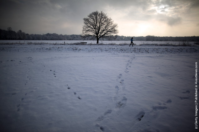 A woman jogs through the snow on Wimbledon common on February