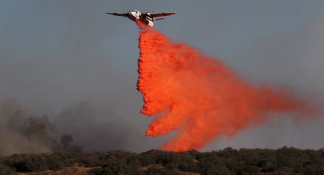 Air tankers make drops at the North Fire near the Phelan, California July 17, 2015. A fast-moving brush fire in the Southern California foothills overran a packed freeway in a mountain pass on Friday, destroying four structures and torching 20 vehicles as drivers abandoned their cars and scrambled to safety. (Photo by Gene Blevins/Reuters)