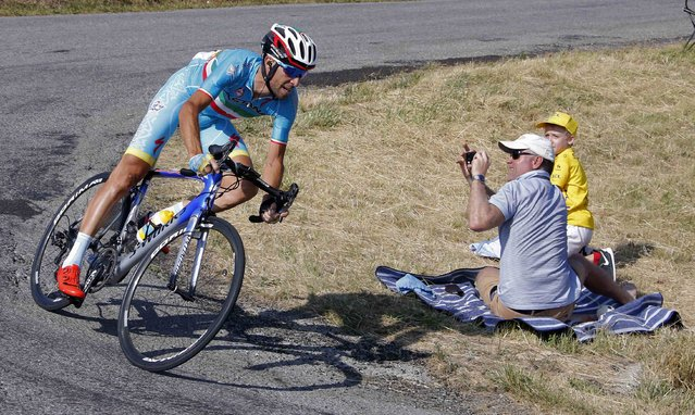 A cycling supporter makes pictures as Astana rider Vincenzo Nibali of Italy speeds along the Manse pass during the 201-km (124 miles) 16th stage of the 102nd Tour de France cycling race from Bourg-de-Peage to Gap, France, July 20, 2015. (Photo by Eric Gaillard/Reuters)