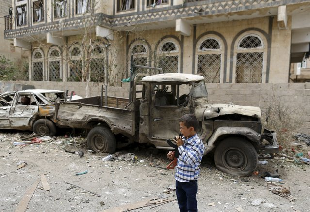 A boy holding a toy rifle stands at the site of a car bomb attack in Yemen's capital Sanaa July 21, 2015. Islamic State's Yemen branch claimed responsibility for a car blast outside a mosque used by the Houthi group on Monday that police sources and medics said killed five people and wounded seven others. (Photo by Khaled Abdullah/Reuters)