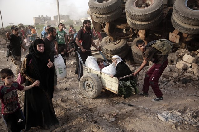 In this Wednesday, May 10, 2017 photo, an elderly woman and a child are pulled on a cart as civilians flee heavy fighting between Islamic State militants and Iraqi special forces in western Mosul, Iraq. (Photo by Maya Alleruzzo/AP Photo)