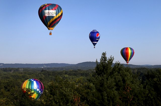 Hot air balloons fly above the trees as seen from a flying balloon just after sunrise on day one of the 2015 New Jersey Festival of Ballooning in Readington, New Jersey, July 24, 2015. (Photo by Mike Segar/Reuters)
