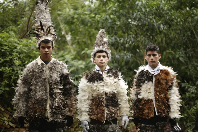 """Catholic parishioners Hector Rafael Villaba, from left, Guillermo Estigarribia, and his brother Jesus, pose in their bird-feather suits during the feast day celebrations honoring St. Francisco Solano, in Emboscada, Paraguay, Friday, July 24, 2015. The feast is a mix of Indian and Catholic beliefs, known by the Guarani name, """"Guaicuru I nemonde"""", which in English translates to """"Dress of the Indigenous"""". (Photo by Jorge Saenz/AP Photo)"""