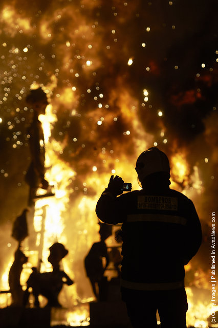 A fireman takes a picture while a combustible 'Ninot' caricatures burn during the last day of the 'Fallas' festival on March 19, 2012 in Valencia, Spain