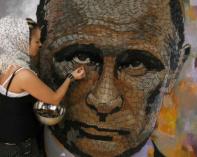 """Ukrainian artist Dariya Marchenko works on a portrait of Russian President Vladimir Putin named """"The Face of War"""" which is made out of 5,000 cartridges brought from the frontline in eastern Ukraine, in Kiev, July 23, 2015. (Photo by Gleb Garanich/Reuters)"""