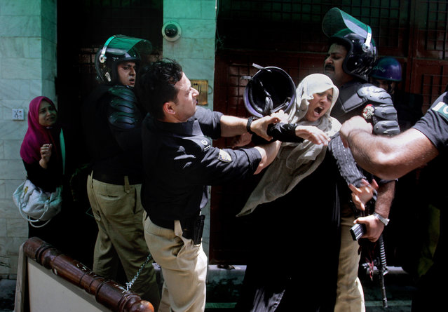 A Pakistani police officer scuffles with a female protester during clashes in Lahore, Pakistan, Tuesday, June 17, 2014.  Police clashed Tuesday with followers of an anti-Taliban cleric critical of Pakistan's government in the eastern city of Lahore, violence that killed at least five people, officials said. (Photo by K.M. Chaudary/AP Photo)