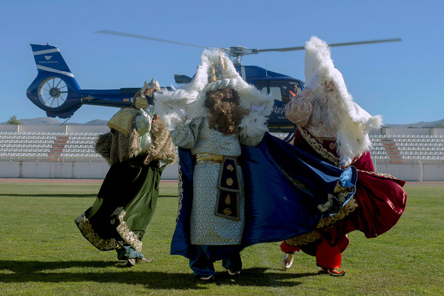 Men dressed up as Balthasar, Gaspar and Melchior, the Three Wise Men, protect themselves from the wind of a helicopter after arriving in it to participate in the Epiphany parade in Ronda, near Malaga, southern Spain January 5, 2019. (Photo by Jon Nazca/Reuters)