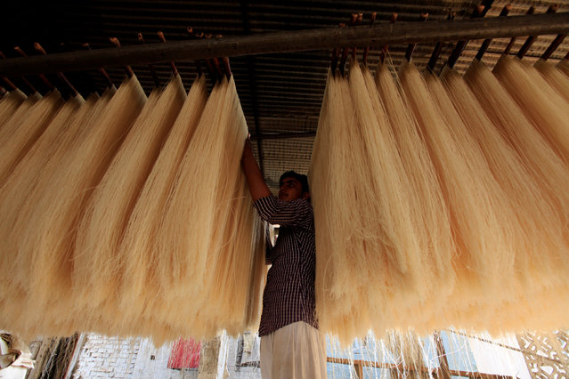 A workers removes dried vermacelli to bake ahead of Ramadan in Rawalpindi, Pakistan, June 1, 2016. (Photo by Faisal Mahmood/Reuters)