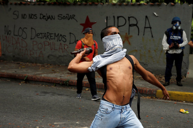 A demonstrator attempts to throw a bottle towards riot police officers during a protest called by university students against Venezuela's government in Caracas, Venezuela, June 9, 2016. (Photo by Carlos Garcia Rawlins/Reuters)