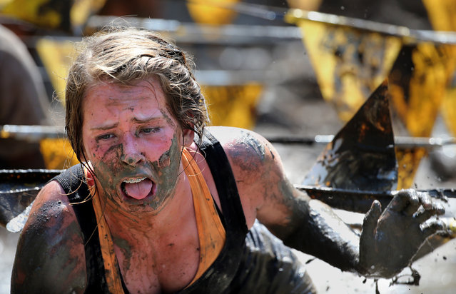 Taylor Poore of Savannah gasps for air after climbing through a mud pit during the 2014 JCB Mud Run in Savannah, Ga., Saturday, June 21, 2014. Race officials said over $100,000 in charitable proceeds from the race will go directly to an early childhood development charity. (Photo by Stephen B. Morton/AP Photo)