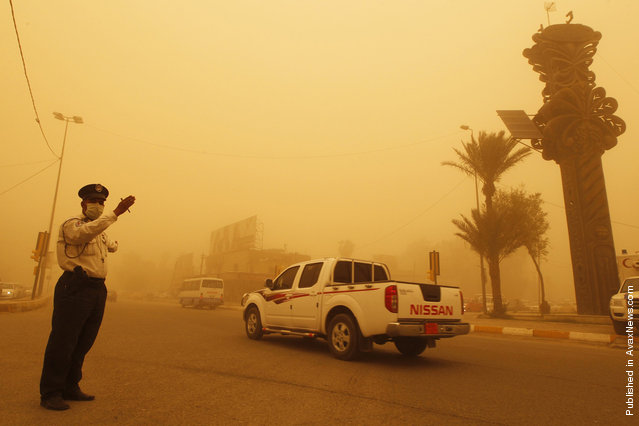 A traffic policeman directs vehicles during a sandstorm in Baghdad's Karrada district April 19, 2012