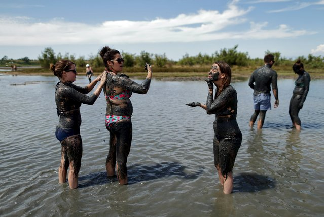 Girls smear each other with mud that is believed to be curative at Queen's beach in Nin, south Croatia, August 2, 2015. (Photo by Antonio Bronic/Reuters)
