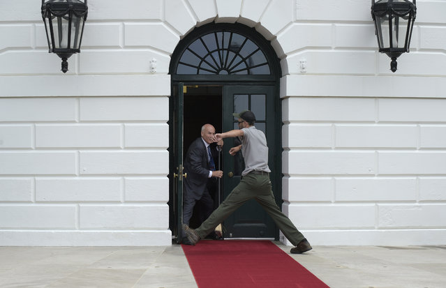 A worker jumps over the red carpet as White House event usher Daniel Shanks sweeps it clean in preparation for President Donald Trump and first lady Melania Trump welcoming Panamanian President Juan Carlos Varela and his wife Lorena Castillo to the White House in Washington, Monday, June 19, 2017. (Photo by Susan Walsh/AP Photo)