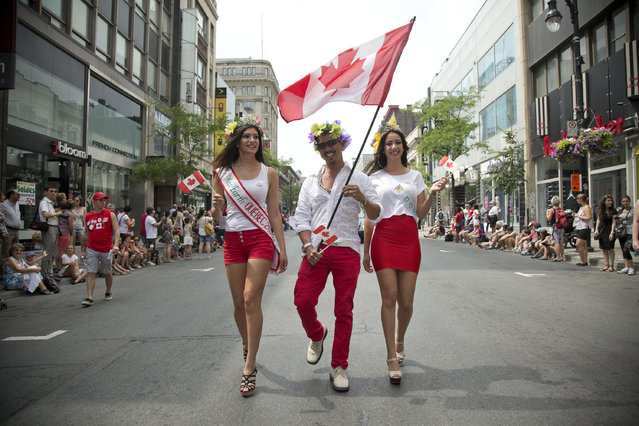 Miss Earth Quebec and Miss Earth Canada assisted the Canada Day Parade  in downtown Montreal, Tuesday July 1, 2014. for viewfinder. (Photo by The Gazette/Vincenzo D'Alto)
