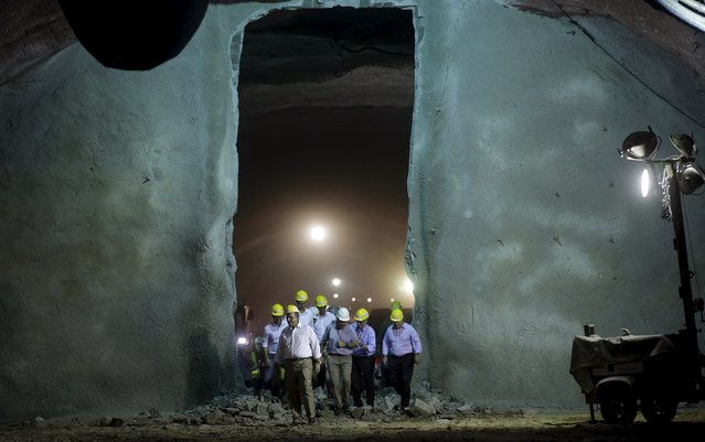 Rio de Janeiro's Governor Luiz Fernando Pezao (2nd L), Rio de Janeiro's Mayor Eduardo Paes (C) and Rio 2016 Olympic Games Organising Committee President Carlos Arthur Nuzman (2nd R) walk trough a wall broken during a ceremony to mark the last detonation of rocks at one of the two tunnels on the Transolimpica freeway route, which will connect the Rio 2016 Olympic Park and the Deodoro Sports Complex, in Rio de Janeiro, Brazil August 4, 2015. (Photo by Ricardo Moraes/Reuters)