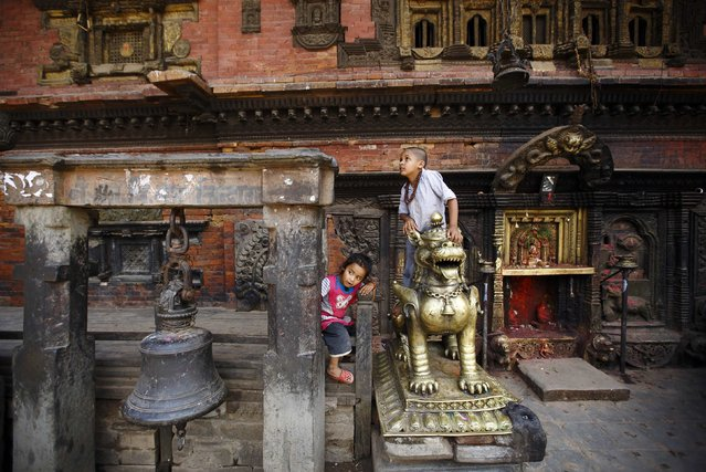 Children play outside a temple along the street in the ancient city of Bhaktapur near Nepal's capital Kathmandu July 2, 2014. (Photo by Navesh Chitrakar/Reuters)
