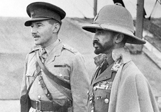 Haile Selassie (right), exiled Emperor of Ethiopia, whose empire was absorbed by Italy, returns with an Ethiopian army recruited to aid the British in Africa, on February 19, 1941. Here, the emperor inspects an airport, an interpreter at his side. On May 5, 1941, after the Italians in Ethiopia were defeated by Allied troops, Selassie returned to Addis Ababa, and resumed his position as ruler