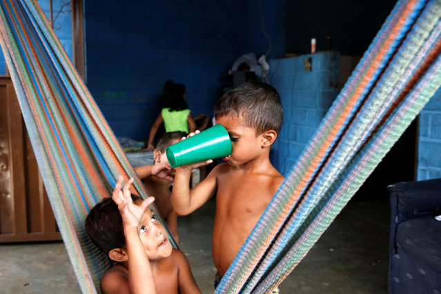 Sharon Roa's sons drink from a plastic cup at their house in La Fria, Venezuela, June 2, 2016. (Photo by Carlos Garcia Rawlins/Reuters)