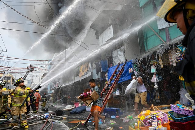 Firefighters work at the scene of a fire at an informal settlement in Manila on October 22, 2019. (Photo by Ted Aljibe/AFP Photo)