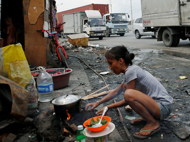 A housewife whose family lives in a shanty cooks beside a road in Manila, Philippines May 25, 2016. (Photo by Erik De Castro/Reuters)