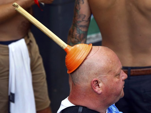 Football Soccer, EURO 2016, Saint Etienne, France on June 20, 2016. An England fan wears a sink plunger on his head in Saint Etienne, France. (Photo by Wolfgang Rattay/Reuters)