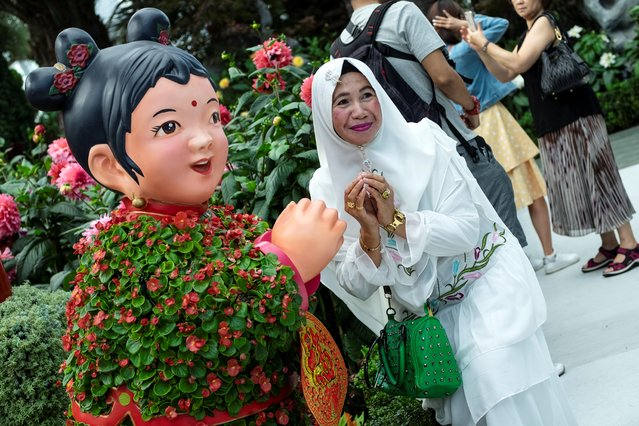 A woman poses with a sculpture of a girl in traditional Chinese attire during the annual Dahlia Dreams floral display which celebrates the upcoming Lunar New Year of the Rat at Singapore's Gardens by the Bay, January 19, 2020. (Photo by Loriene Perera/Reuters)