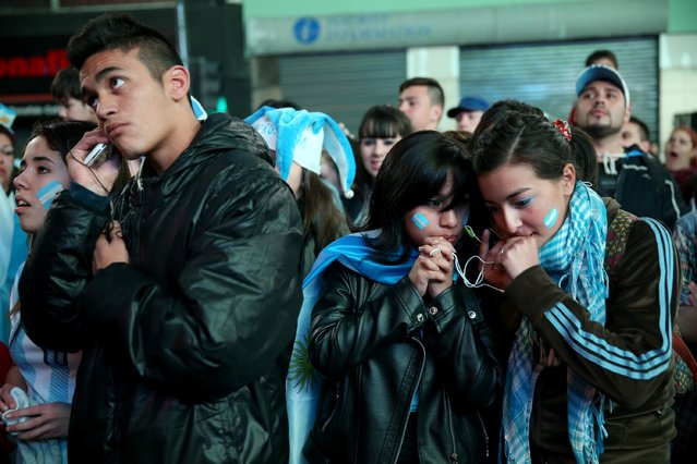 Argentine soccer fans react while watching a television broadcast as time runs out against Germany during the World Cup final on July 13, 2014 in Buenos Aires, Argentina. Germany won 1-0 for their fourth World Cup title, played in Rio de Janeiro. (Photo by Joe Raedle/Getty Images)