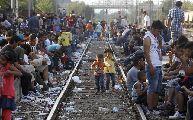 Migrants wait for a train towards Serbia, at the railway station in the southern Macedonian town of Gevgelija, Wednesday, August 12, 2015. (Photo by Boris Grdanoski/AP Photo)