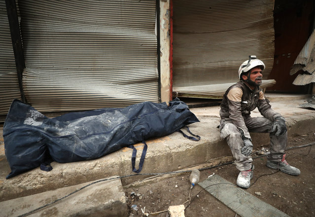 A member of the rescue workers known as the White Helmets sits near a body bag containing the body a victim uremoved from the rubble of a building, hit during an air strike by pro-regime forces on the rebel-held town of Ariha in the northern countryside of Syria's Idlib province, on February 5, 2020. Syrian regime forces pressed on with their offensive in the northwest that has displaced half a million people, despite heightened tensions with Turkey. Intensive aerial bombardment and ground fighting in the jihadist-dominated Idlib region since December have killed almost 300 civilians and triggered one of the largest waves of displacement in the nine-year war. (Photo by Omar Haj Kadour/AFP Photo)