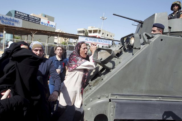 A woman trying to close the road gestures on a Lebanese army tank during a protest against the detention of Sheikh Ahmed al-Assir by Lebanese authorities, in Sidon, south Lebanon August 15, 2015. (Photo by Ali Hashisho/Reuters)