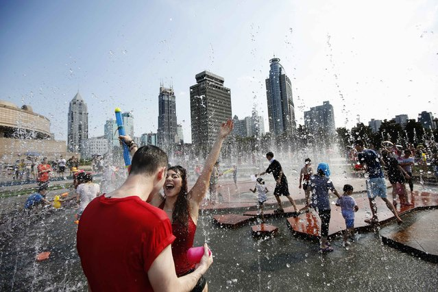 People participate in a water fight at People Square in Shanghai, July 20, 2014. (Photo by Aly Song/Reuters)