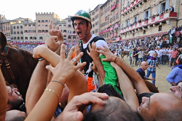 "Jockey Giovanni Atzeni (C) also known as ""Tittia"" of Siena's city quarter Selva celebrates after winning the Palio della Madonna dell'Assunta horse race with his horse Polonki in Siena, Italy, 17 August 2015. The Palio della Madonna dell'Assunta is held twice each year on July and August and is one of the world's most important horse races. (Photo by Maurizio Degl'innocenti/EPA)"